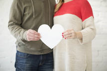 couple holding a paper heart cutout