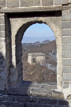 Chinese mountainside seen through an arched window at the Great Wall of China
