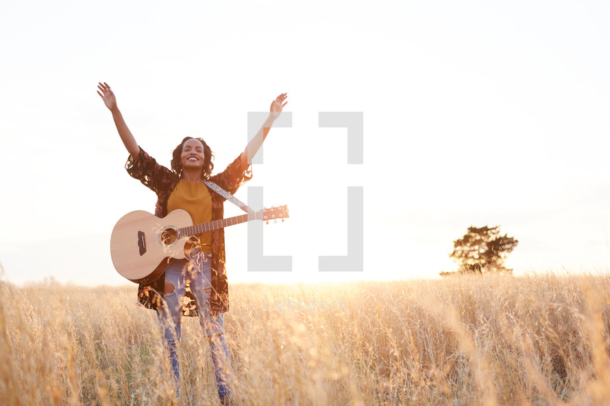 a woman standing in a field with a guitar with hands raised