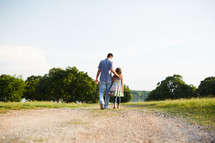 a father and daughter walking down a dirt road talking