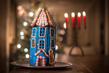 a gingerbread house and bokeh candlelight and Christmas tree lights in the background