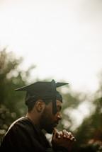 praying male graduate