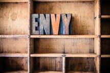 "Wooden letters spelling ""envy"" on a wooden bookshelf."