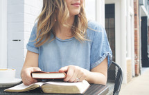 a young woman sitting at an outdoor table with a Bible and journal