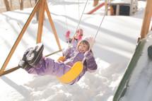 kids on a backyard swings in the snow