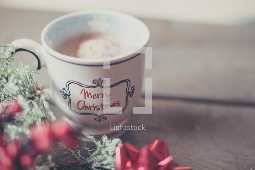 a Merry Christmas mug and holly
