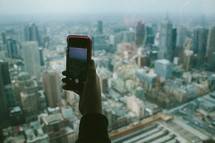 hand holding up a cellphone in front of a cityscape