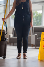 woman with a mop and mop bucket