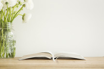 white flowers in a vase and open Bible