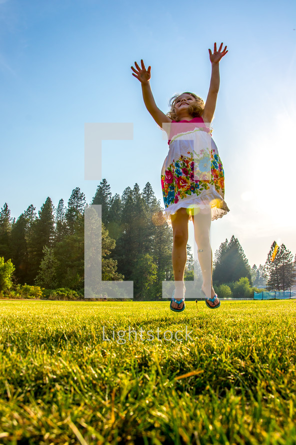 little girl jumping in the grass