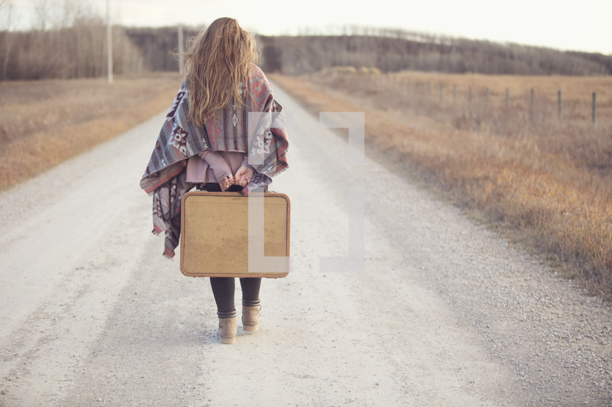 a young woman with suitcase travelling up the road