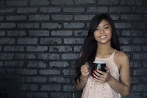 A smiling young woman holding coffee cup and standing against a gray brick wall.