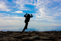 Silhouette of a person in a hoodie jumping for joy on the beach near the ocean.