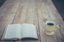 open Bible and coffee mug on a wood table