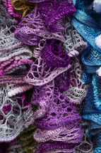 Pile of knitted scarves.