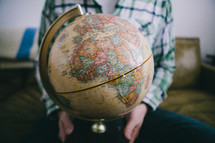 A man sits holding a globe.