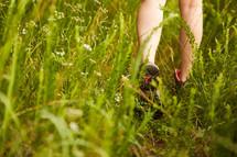 man walking through thick grass
