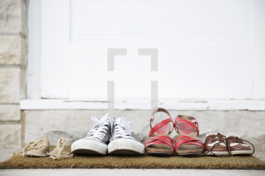 row of shoes on a doormat