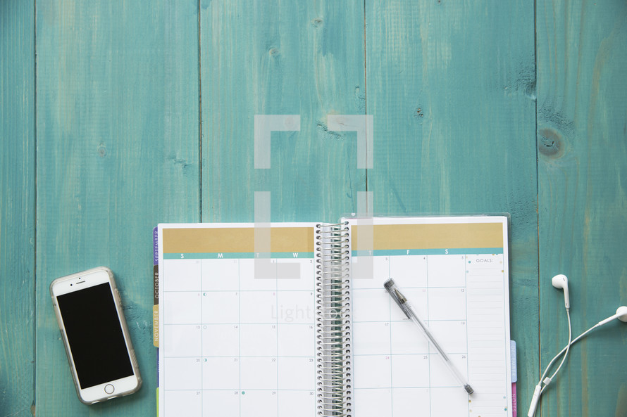 iPhone, planner, earbuds, and pen on teal blue background