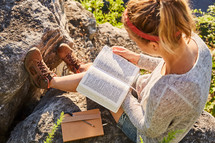 A woman sitting on a rock outdoors reading her Bible and journaling