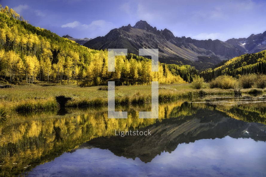 Mt Sneffels and Aspen trees reflecting in a beaver pond in the Colorado San Juan Mountain range in the fall season