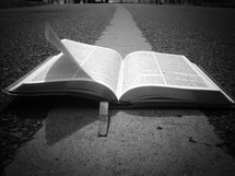 open Bible on the center lines of a road