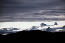 clouds over snow capped mountain peaks