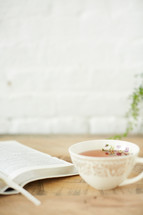 open Bible and tea cup on a table