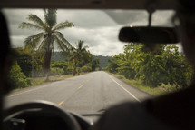 vehicle driving down a road lined with palm trees