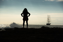 silhouette of a woman standing on an ocean shore looking out at a ship