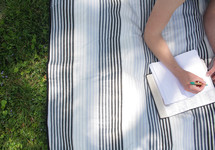 a girl lying on a blanket in the grass reading a Bible and writing in a journal