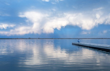 man standing at the end of a dock on a lake under a cloudy sky