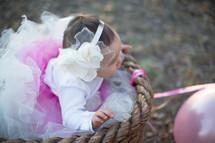 toddler girl in a tutu in a basket