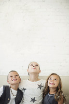 kids sitting together on a couch looking up.