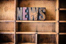 "Wooden letters spelling ""news"" on a wooden bookshelf."