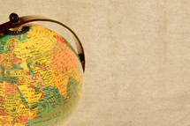 World globe against a beige paper background showing the middle east