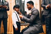 groom adjusting ring bearers suspenders