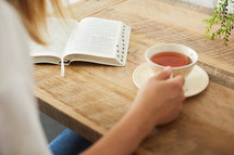 a woman with a tea cup reading a Bible