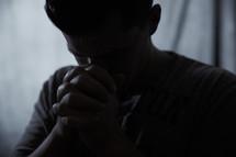 man praying in darkness
