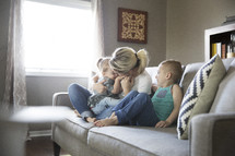 children sitting on the couch with mom.