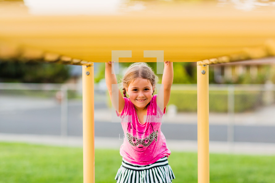 Elementary girl on the monkey bars, smile, joy, back to school, happy, playground