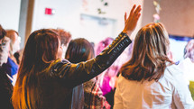 women with raised hands at a conference