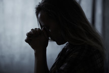 a woman praying in darkness