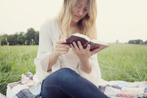woman sitting outdoors reading a book