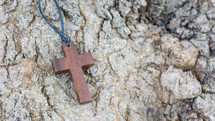 wooden cross necklace on a rock