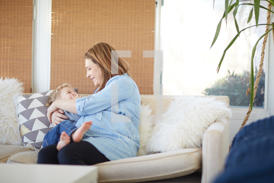 a mother snuggling her son sitting on a couch