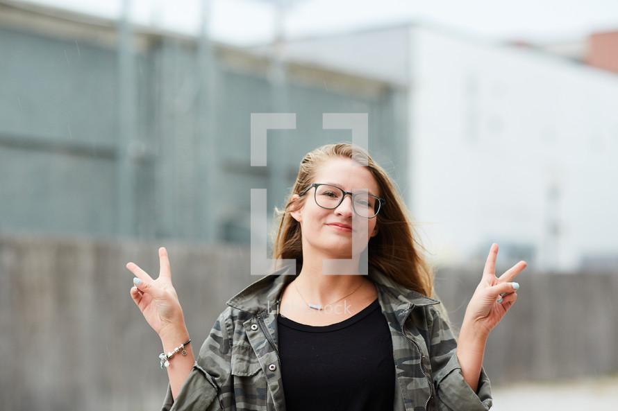 teen girl flashing peace signs