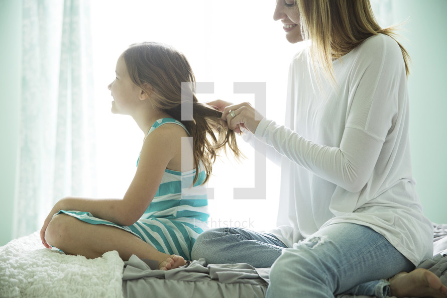 a mother braiding her daughter's hair