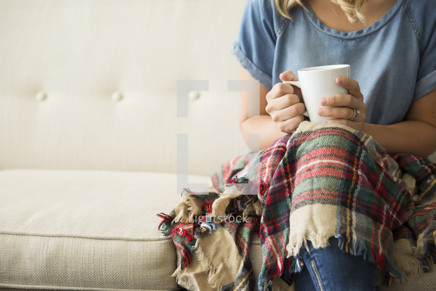 a woman sitting on a couch with a plaid blanket in her lap holding a mug
