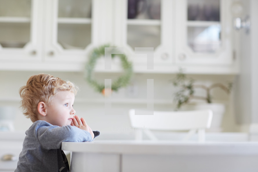 a toddler sitting at a kitchen table praying